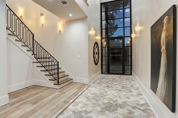 The elegant entry opens to a stunningly vibrant interior which effortlessly exudes a refined lifestyle. Antique brick placed in a Herringbone pattern throughout the entry way with 20' ceilings. Sleek walls & glass entry wall with aluminum trim punctuate t (photo 4)