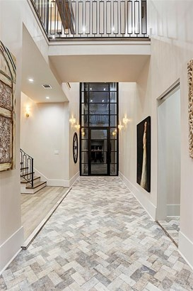 """Perspective from the Great Room towards the entry with a southern exposure glass door. Contrasting 7"""" Oak flooring & Antique placed brick. Sliding door on right leads residents the MUD room. (photo 5)"""