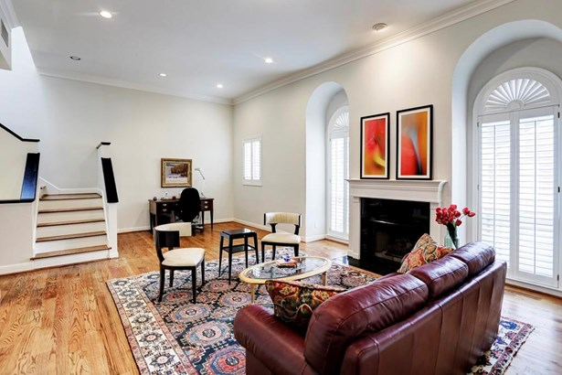 Overview of the living room space with beautiful arched windows, fireplace, bar and gleaming wood floors. (photo 3)