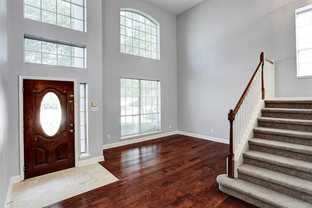 Wood and glass door opens into this two story formal living area (photo 3)