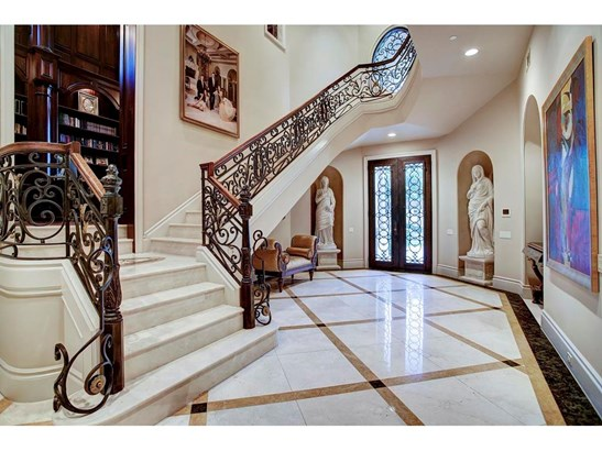 Stunning entry with polished marble flooring and four marble statues, included in sale, representing the four seasons. Views of the two story library/study can be seen. (photo 2)