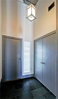 Upon entry you are greeted with a stylish pendant illuminating the 12x24 dark floor tiles. 14 ft ceilings are carried throughout. (photo 3)