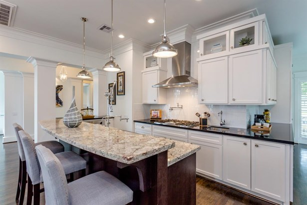 """The kitchen features high grade granite counters, two sinks, a pot filler, Sub-Zero fridge, Blue Star commercial grade 36"""" wall oven, 36"""" stove top and two dishwasher drawers. (photo 5)"""