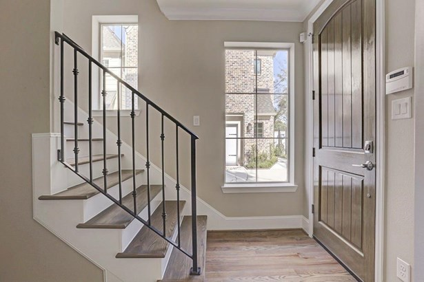 View of entryway and foyer with solid wood door and solid wrought iron staircase with simplistic spindles. Unit J has not yet started. (photo 5)