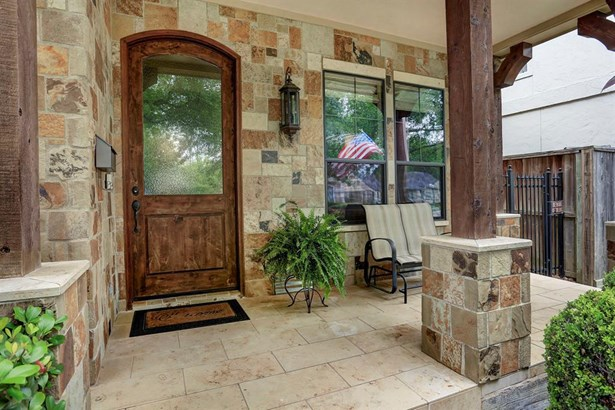 The large natural stone front porch has cedar pillars. (photo 4)