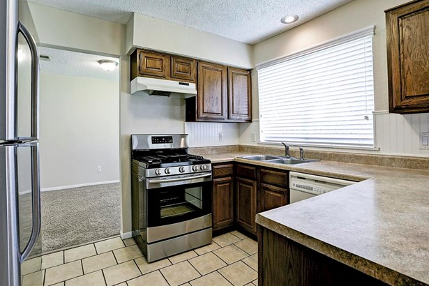 Light and bright kitchen features stainless gas stove. (photo 5)