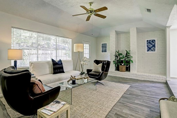 Light and bright living room with wood-like tile flooring throughout, exposed brick fireplace (photo 1)