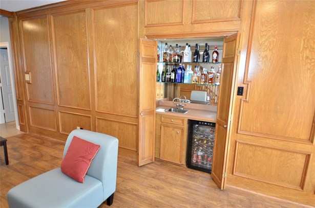 Open one of the wooden panels & poof, there's your wet bar! (photo 5)