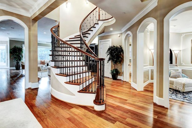 Beautiful Entry Way with spiral staircase, hardwood floors, crown molding and open concept living spaces. (photo 2)