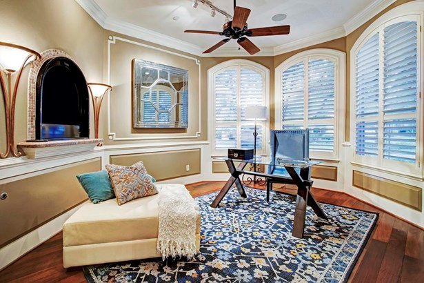 The Formal Living Room comes complete with plantation shutters, gas log fireplace, crown molding, hardwood flooring, and beautifully detailed mill work. (photo 3)