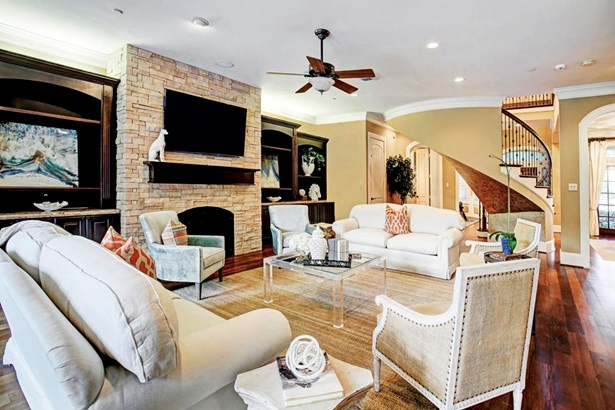 The Den is a large relaxing space with plenty of storage thanks to the dual built-ins, handsome stone - gas fireplace, crown molding, hardwood floors, and an oversized window with great views of the backyard and pool. (photo 5)