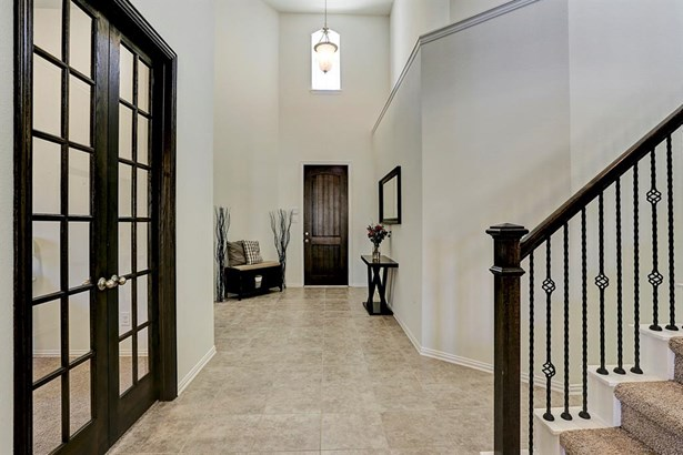 Light and bright foyer with a gorgeous wooden door and dazzling tiled floors continues into the living room. Pictured on the left is the downstairs flex room which is currently being used as an office. (photo 2)
