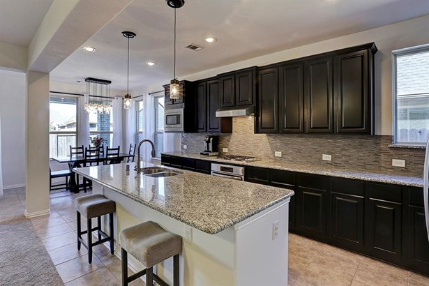 The open kitchen overlooks the light, bright living room and breakfast room. (photo 5)