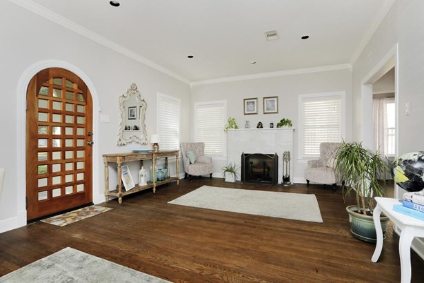 Front door open to this spacious living area. First view, large enough for two sitting areas. High ceilings, crown molding, recessed lighting, wood burning fireplace and wood floors (photo 3)