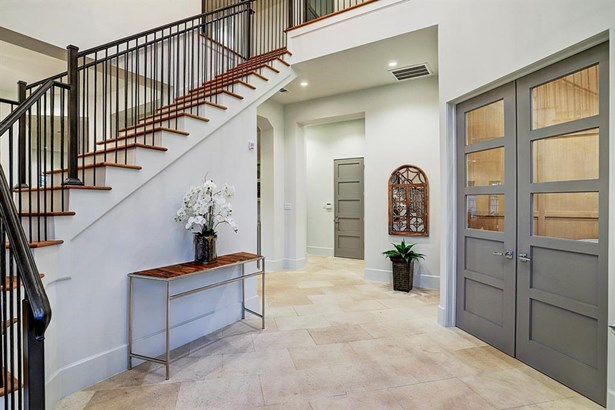 """Through the 9"""" double frame glass entry doors guests are welcomed into the reception hall with winding staircase that boasts select white oak treads and custom designed baluster. (photo 3)"""