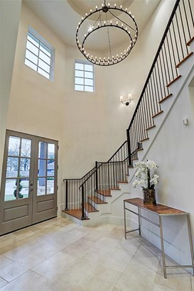 Opposite view of the grand entry with 22' high ceilings. Limestone floors run through the space. French Oak floors contrasted by the custom designed iron balustrade lead you to the 2nd level. Library/ Study located to the left through a double door entry. (photo 4)