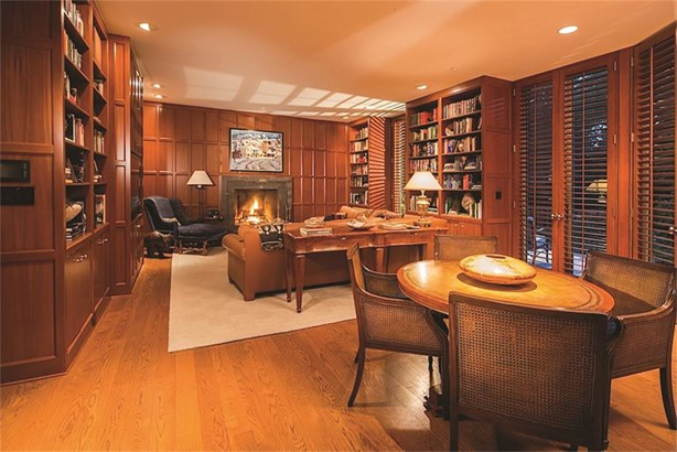 Richly stained cherry wood paneling lends the perfect touch to this great library and family room with three sets of shuttered French doors along the entire west wall. (photo 5)