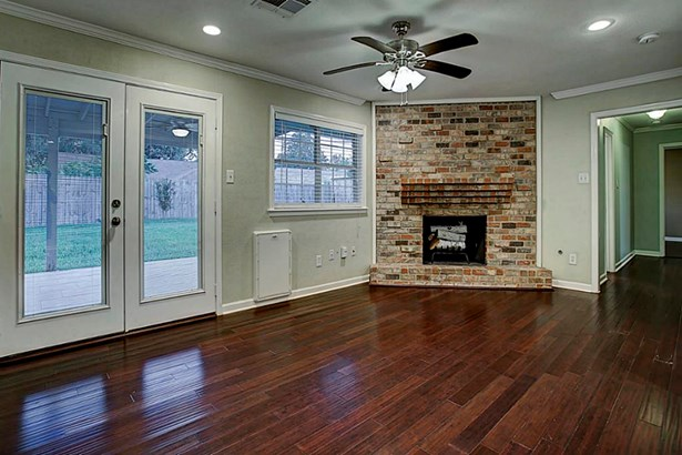 Corner gas/wood burning fireplace anchors the room and provides a nice focal point. Double doors lead to the covered back patio. (photo 4)