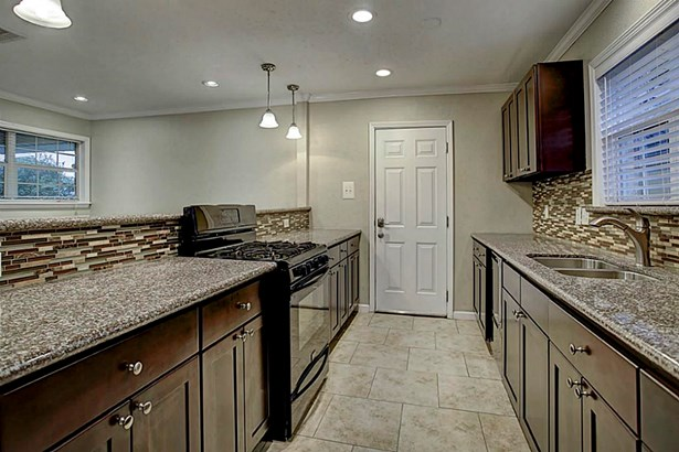 Galley style kitchen boasts granite countertops, gas cooking, dual basin sink and ample cabinet as well as prep space. (photo 5)