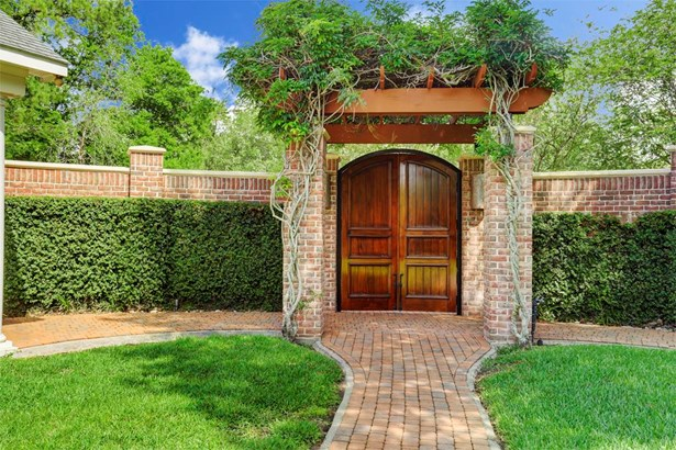 From the enormous parking and drive area, one steps through these lovely mahogany gates and vine covered pergola to view out onto the vast lawn. You have entered luxury compound living at its finest. (photo 3)