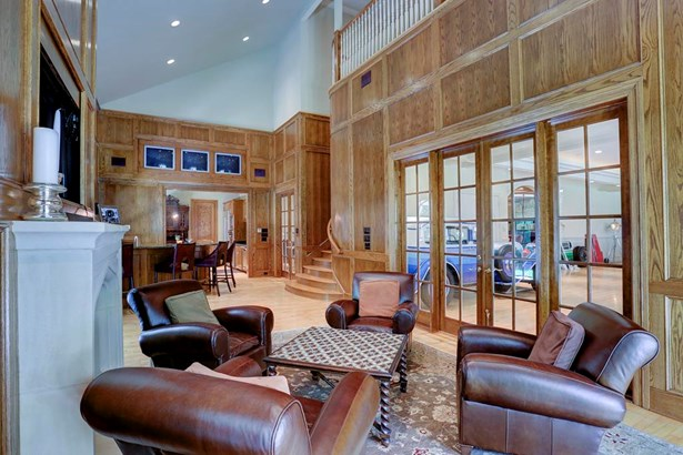 From the beautifully paneled family room/den area, one can look into one of two very large areas which currently showcase an auto collection. It would be easy to reconfigure into more traditional living spaces or keep as is for your collection! (photo 5)