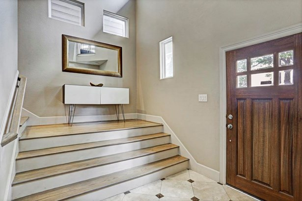 Upon entrance you are greeted by an open foyer with tile floors and neutral paint. There is a bedroom with en-suite bathroom and access to the two car garage from the first floor. (photo 2)