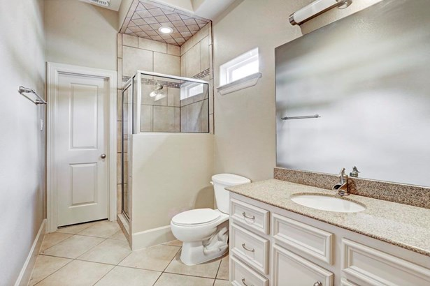 The first floor en-suite bathroom features a shower, vanity with granite countertop + cabinets/drawers for storage space, and large walk in closer. The neutral tile flooring and paint tones keep the area bright. (photo 4)