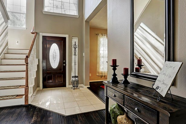 Wonderful light filled two story entry foyer with tile floors and laminate hardwood stair case. (photo 3)