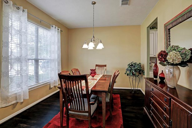 Large formal dining room with decorator paint, laminate floors, two window blinds and satin nickel candelabra. (photo 4)