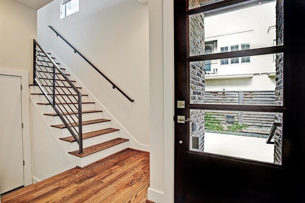 The front door is custom mahogany and glass and opens to a spacious entry. Step down to the left and the door leads to the garage. Stairs on the right lead to the second floor living area. (photo 2)
