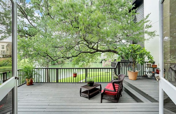 Glass double doors open to a spacious back patio with picturesque views of the lake (photo 2)