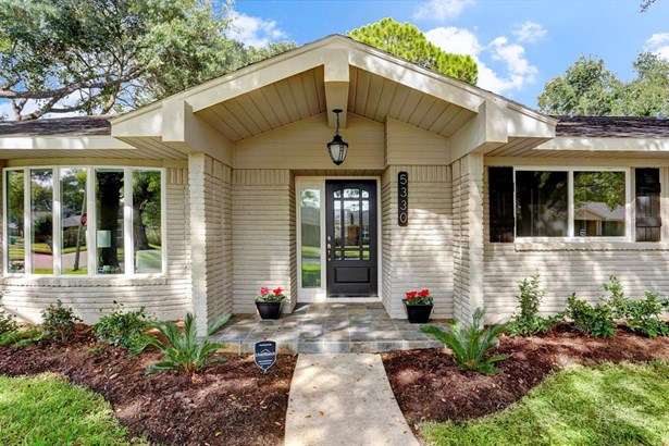 The home has a large front patio and front door with leaded glass inserts. (photo 3)