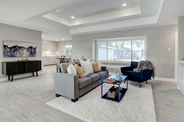 The 21x27 SF living room has raised ceilings with recessed lighting and window seat. (photo 4)