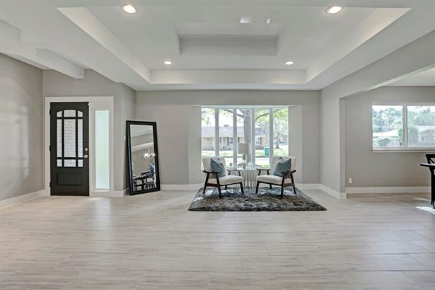 Living room with view of the front door. The home has tile floor throughout. (photo 5)