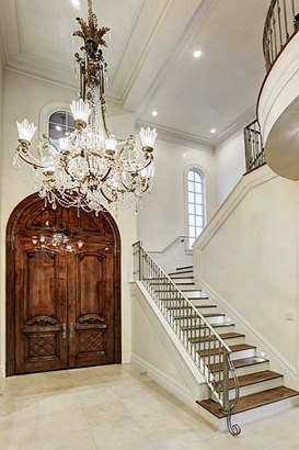 Alternate perspective of entry highlights the monumental double-door entry accented with intricate molding details. The grand staircase with European White Oak treads and exceptionally custom designed balustrade takes you to the second level. (photo 5)