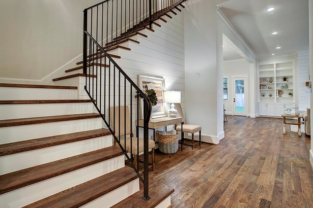 Solid wrought iron baluster and simplistic spindles are complimented by ship lap detailing, wide plank white oak flooring and solid wood stair treads. (photo 5)