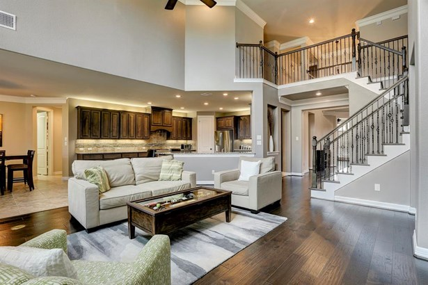 The 2-story ceiling in the family room/den is amazing and allows for lots of natural light. Plenty of room for various furniture configurations. (photo 1)