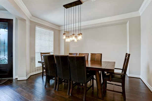 The formal dining room is located just off the entry and features dark wood flooring, large window, high ceilings with moldings and a decorative light fixture. (photo 4)