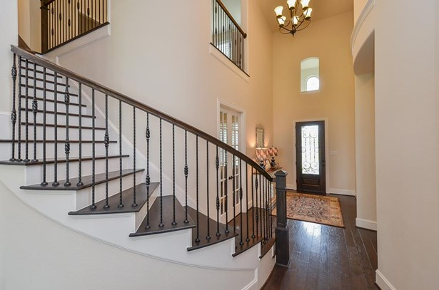Tall ceiling and a wide entrance greets your guests. Notice the lovely curved staircase. (photo 4)