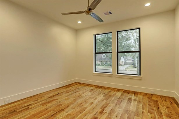 Secondary bedroom with ceiling fan, adjoining bath. (photo 4)