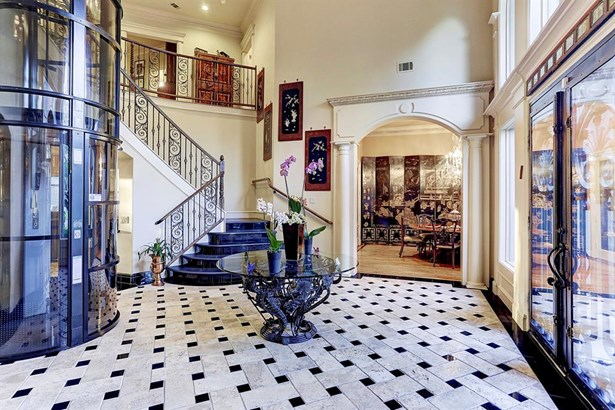 Stunning entrance with walnut travertine in basket weave pattern and granite inserts. The formal dining room is through the arched doorway. (photo 2)