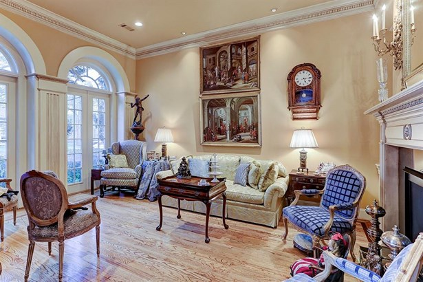 Gracious formal living room with fireplace, oak hardwood floors, crown molding and custom millwork. (photo 3)