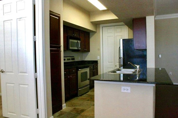 Kitchen featuring stainless steel appliances, granite counter tops and in unit laundry just beyond the kitchen. (photo 3)