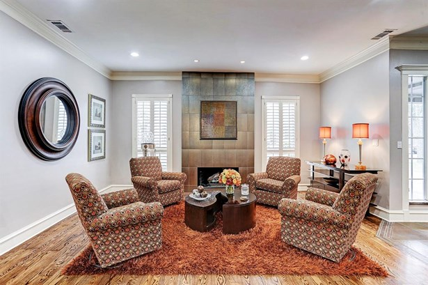 Formal living room has hardwood floors, plantation shutters, gas log fireplace with amazing surround. (photo 4)