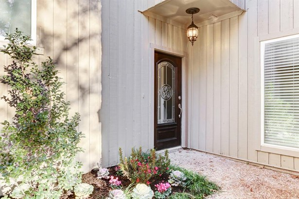 A private walkway winds around to the front door of the townhome. Note the mahogany front door inset with beveled glass and new hardware as well as the replaced light fixture above. Walking up, one is delighted by the fresh, colorful landscaping. (photo 2)