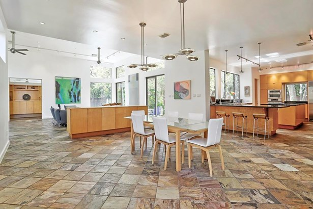 [Main Gathering Space]Encompasses the great room, dining room and kitchen. Soaring ceilings, designer pendant and track lighting, slate floors, banks of tall windows and heavy sliding doors bring the outside in. (photo 4)