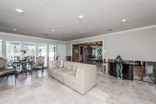 Stone flooring remains throughout the family room, kitchen and baths. A wall of recently replaced windows along the back of the home allows wonderful natural light with added accents of recessed lighting and crown molding. The open wall between kitchen an (photo 3)