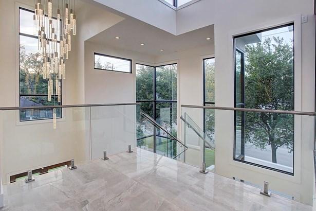Large scale drop chandelier framed by modern glass/steel pony wall. (photo 4)