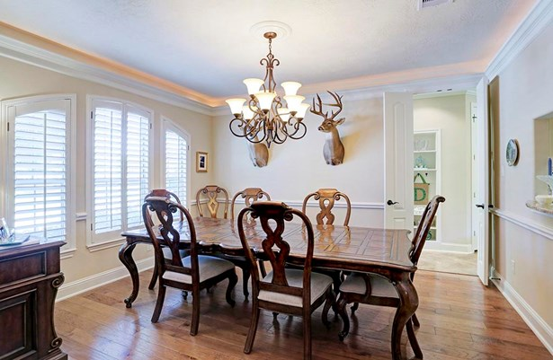 Formal dining room with wide plank wood floors and plantation shutters (photo 3)