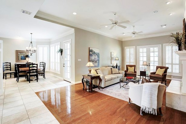 """Family room, breakfast room and kitchen spaces all open. Another view of great windows, and """"Toasty Grey"""" paint color. Tile flooring in breakfast room and kitchen. (photo 3)"""